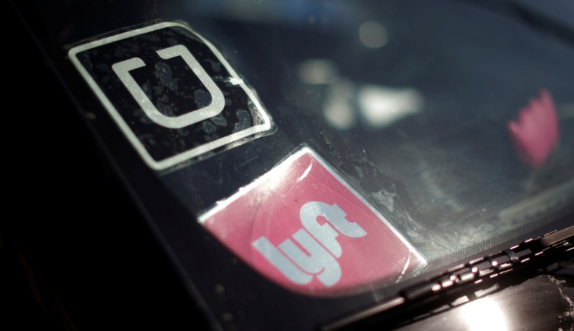 A driver displays Uber and Lyft ride sharing signs on his car windscreen in Santa Monica